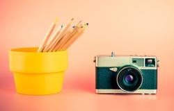 Камера с карандашами crayon цвета на пинке стоковые фото