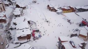 Камера трутня показывает современный, швейцарский малый снег покрытая зона лыжи окруженная холмами акции видеоматериалы