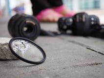 Камера упаденная к земле, причиняя фильтр сломать, поврежденные len и тело В концепции страхования от несчастных случаев дальше стоковое фото