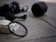 Камера упаденная к земле, причиняя фильтр сломать, поврежденные len и тело В концепции страхования от несчастных случаев дальше стоковое фото rf