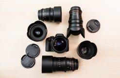 Камера цифров SLR и немного заменимых ручных объективов Оборудование для кинематографии Деревянный стол стоковая фотография