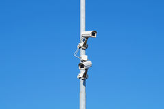 Камеры слежения против Cctv безопасностью голубого неба Стоковые Изображения