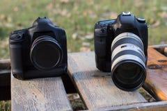 2 камеры с объективами лежат на lounger солнца Стоковые Изображения