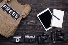 Камеры таблетки и тетради, бронежилета и фото ПК на деревянном t Стоковое Изображение RF