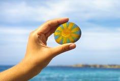 Камешек владением руки персоны с покрашенным ярким солнцем против голубого неба Стоковая Фотография