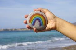 Камешек владением руки женщины с покрашенной радугой против моря Стоковые Изображения RF