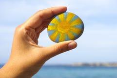 Камешек владением руки женщины с покрашенным ярким солнцем Стоковая Фотография RF
