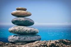 Камешки Дзэн балансируя на предпосылке моря Стоковое Изображение