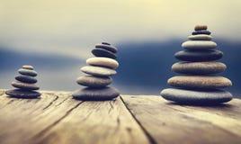 Камешки Дзэн балансируя рядом с туманной концепцией озера Стоковые Фотографии RF