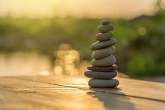 Камешки Дзэн балансируя рядом с туманным озером Стоковое фото RF