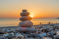 Камешки Дзэн на заходе солнца пляжа Стоковая Фотография RF