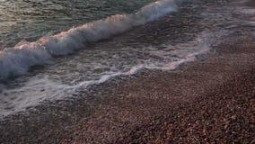 Камешки и волны моря в вечере освещают сток-видео