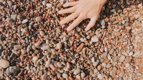 Камешки моря женской руки лаская на пляже акции видеоматериалы