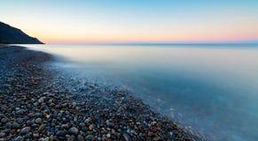 Камешки на пляже причиняя море пропустить вокруг их делая картины Стоковая Фотография RF