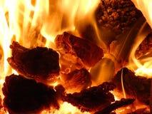 Камин - горячие пламена горящих шишек и жары угля Стоковая Фотография