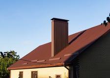 Камин сделанный профилированный покрывать на крыше со сточными канавами дождя и предохранителями снега стоковые фотографии rf
