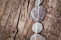 Камни выровнянные на древесине Стоковое Фото
