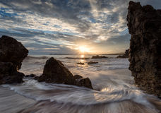 Камни в морской воде на предпосылке захода солнца Стоковое Изображение RF