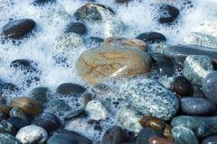 Камни и волны моря на пляже r стоковые фото