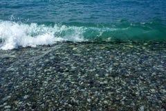 Камни и волны моря на пляже r стоковые фотографии rf