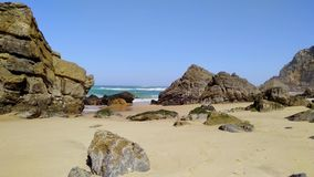 Камни и утесы на песчаном пляже в Португалии западный Атлантический океан видеоматериал