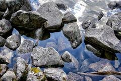 Камни и утесы на прозрачной поверхности озера Стоковое фото RF