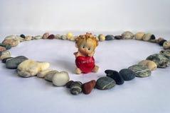 Камни моря клали вне в сердце и figurine ангела Стоковая Фотография