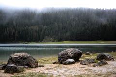 Камни на береге черного озера стоковые изображения