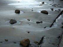 Камни на заходе солнца на пляже стоковая фотография rf