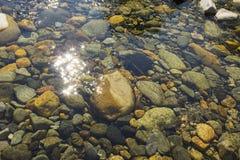 Камни реки с заплатой солнечного света Стоковое Изображение