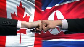 Канада против международных отношений конфликта Северной Кореи, кулаки на предпосылке флага сток-видео