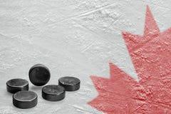 Канадское изображение кленового листа на льде с шайбой хоккея Стоковое Фото