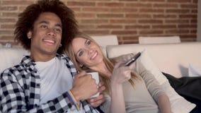 Каналы счастливых молодых пар изменяя с дистанционным управлением пока смотрящ ТВ на софе дома сток-видео