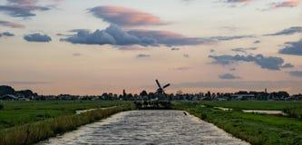 Канал в Голландии со старой ветрянкой на горизонте под красочным небом стоковые изображения rf