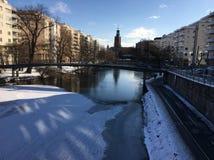 Канал замерли Стокгольмом, который с взглядом к здание муниципалитету Стоковые Изображения RF