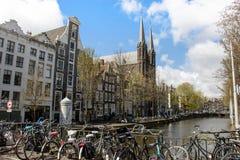 Каналы Амстердама, велосипеды на мосте, красивые дома вдоль реки Стоковые Изображения