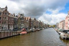 Каналы Амстердама, исторические места Амстердама, красивые дома вдоль реки Стоковая Фотография