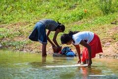 КАНДИ, ШРИ-ЛАНКА - ОКОЛО ДЕКАБРЬ 2013: Неопознанная ткань мытья девушек Sri Lankan Стоковые Фотографии RF