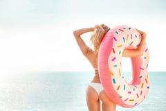 каникула территории лета katya krasnodar Наслаждаться женщиной suntan в белом бикини с тюфяком донута около моря стоковое фото rf