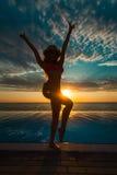 каникула территории лета katya krasnodar Силуэт женщины танцев красоты на заходе солнца около бассейна с видом на океан стоковое фото