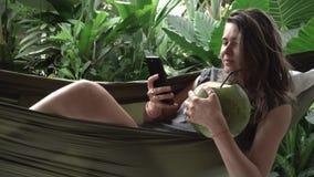 Каникулы в Азии Женщина пишет сообщение на мобильном телефоне, кладет в гамак с кокосом видеоматериал