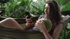 Каникулы в Азии Smartphone пользы женщины, положение в гамаке с кокосом акции видеоматериалы