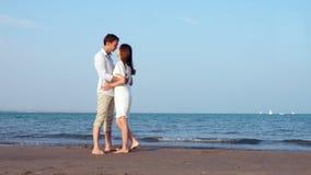 Каникулы соединяют на пляже на руках и целовать захода солнца романтичных держа сток-видео