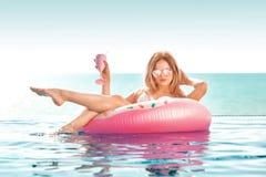 каникула территории лета katya krasnodar Женщина в бикини на раздувном тюфяке донута в бассейне КУРОРТА стоковая фотография rf