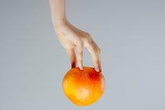 каникула территории лета katya krasnodar Цитрусовые фрукты грейпфрута с выпивая соломой в женской руке на сером цвете еда питья з Стоковое Изображение RF