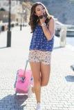 Каникулы девушки идя с розовым чемоданом Стоковая Фотография
