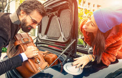 Каникулы красивых пар моды идя, нагружая их автомобиль стоковая фотография
