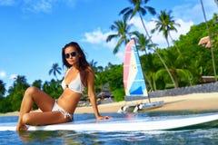 Каникулы перемещения Женщина на борту в море девушки стола голубого мальчика смотрят заниматься серфингом моря сидя спорты Стоковые Изображения