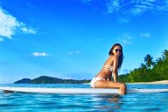 Каникулы перемещения Женщина на борту в море девушки стола голубого мальчика смотрят заниматься серфингом моря сидя спорты Стоковое Изображение