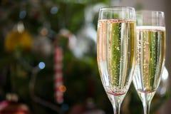 2 каннелюры Шампани на предпосылке рождества Стоковое Фото